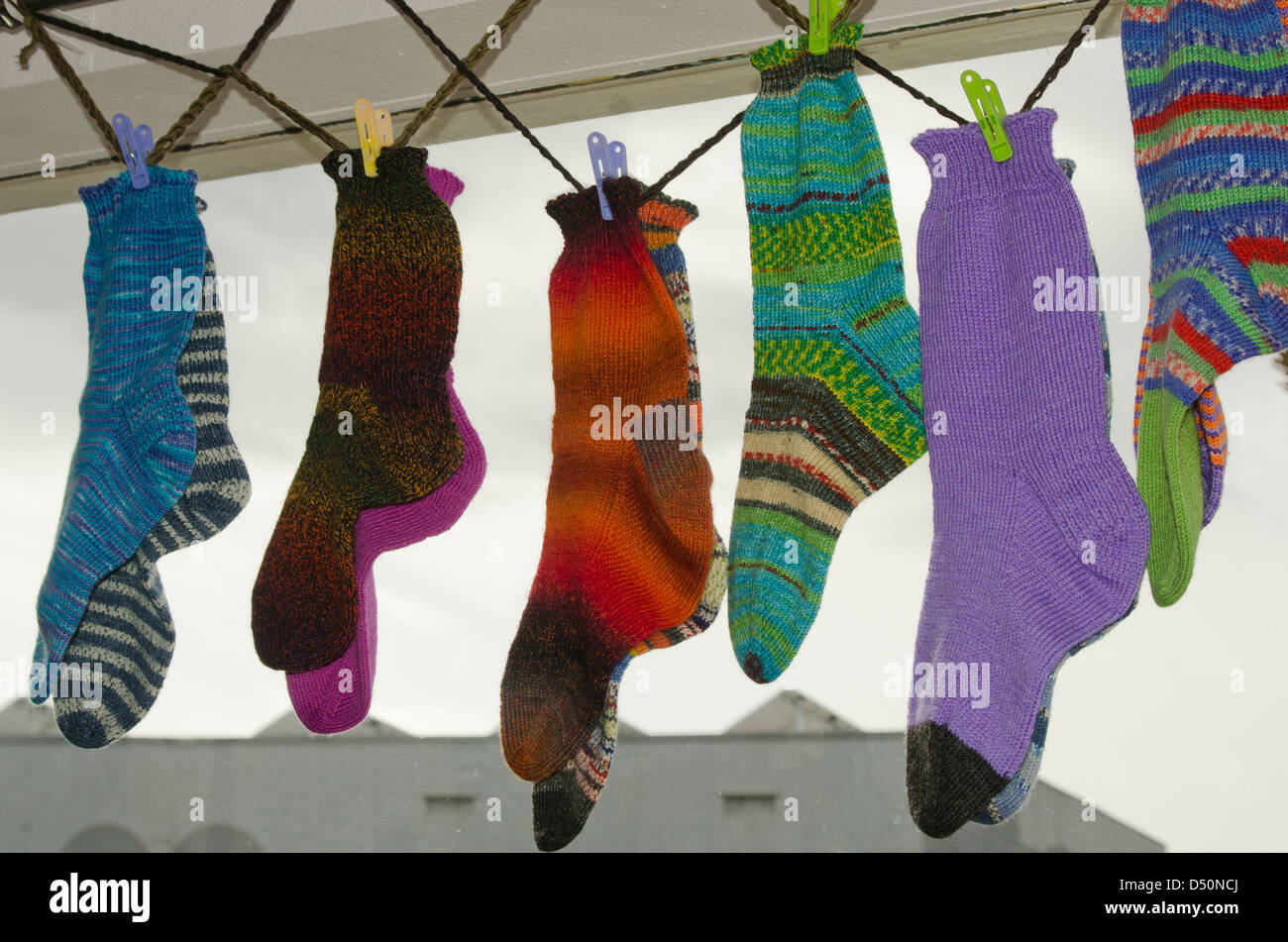 Several pair of wool socks hang in a shop window, enticing buyers thinking about oncoming winter cold. - Stock Image