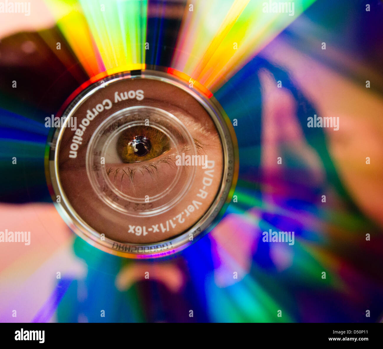 Close up of an eye seen through the hole of a Sony DVD-R - Stock Image