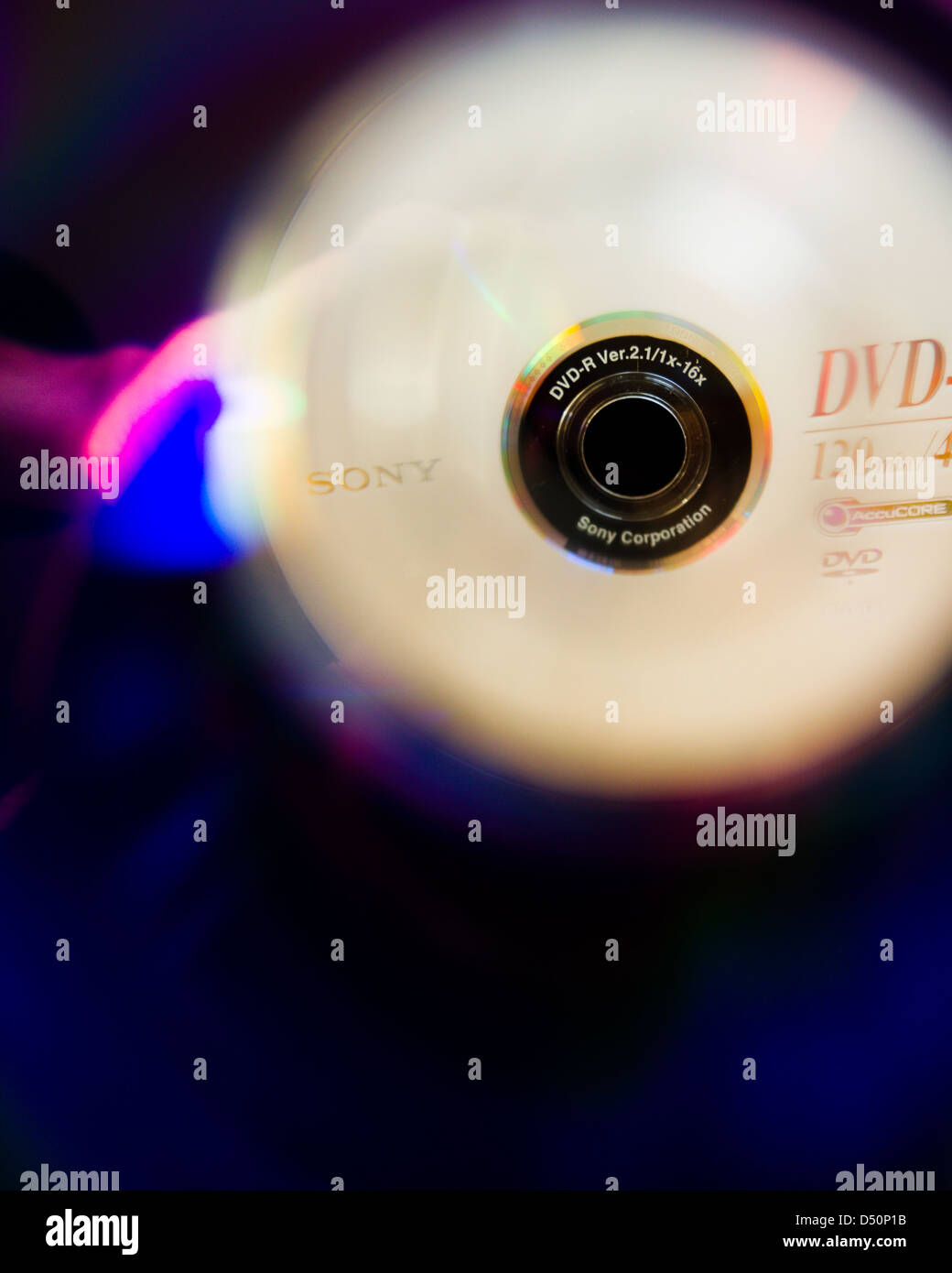 A DVD-R close up, seen as a reflection viewed through the hole in the centre - Stock Image