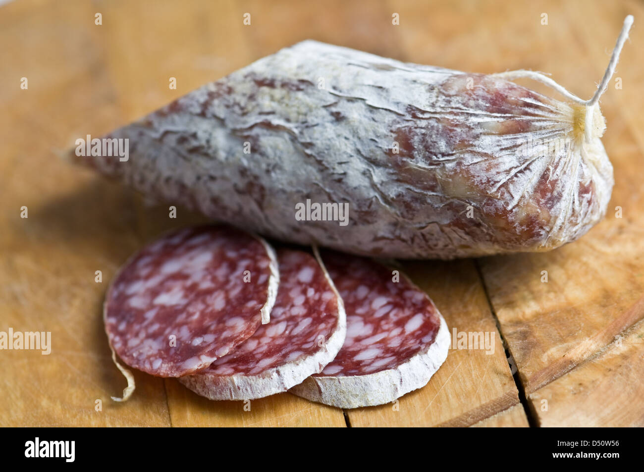 salami pieces on wood table - Stock Image