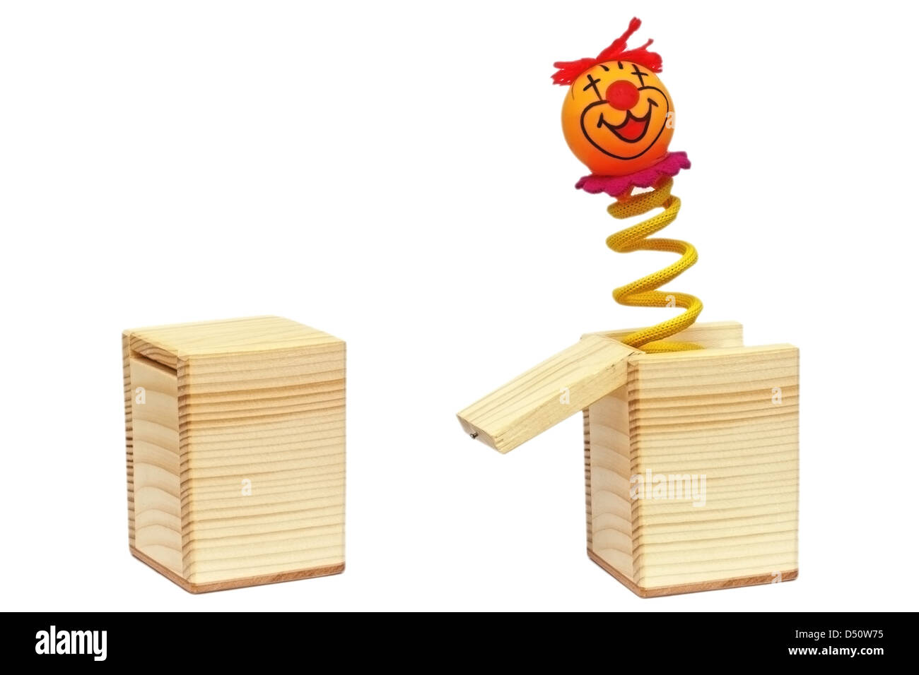 tricky toy with clown on spring coming out from a wooden box - Stock Image