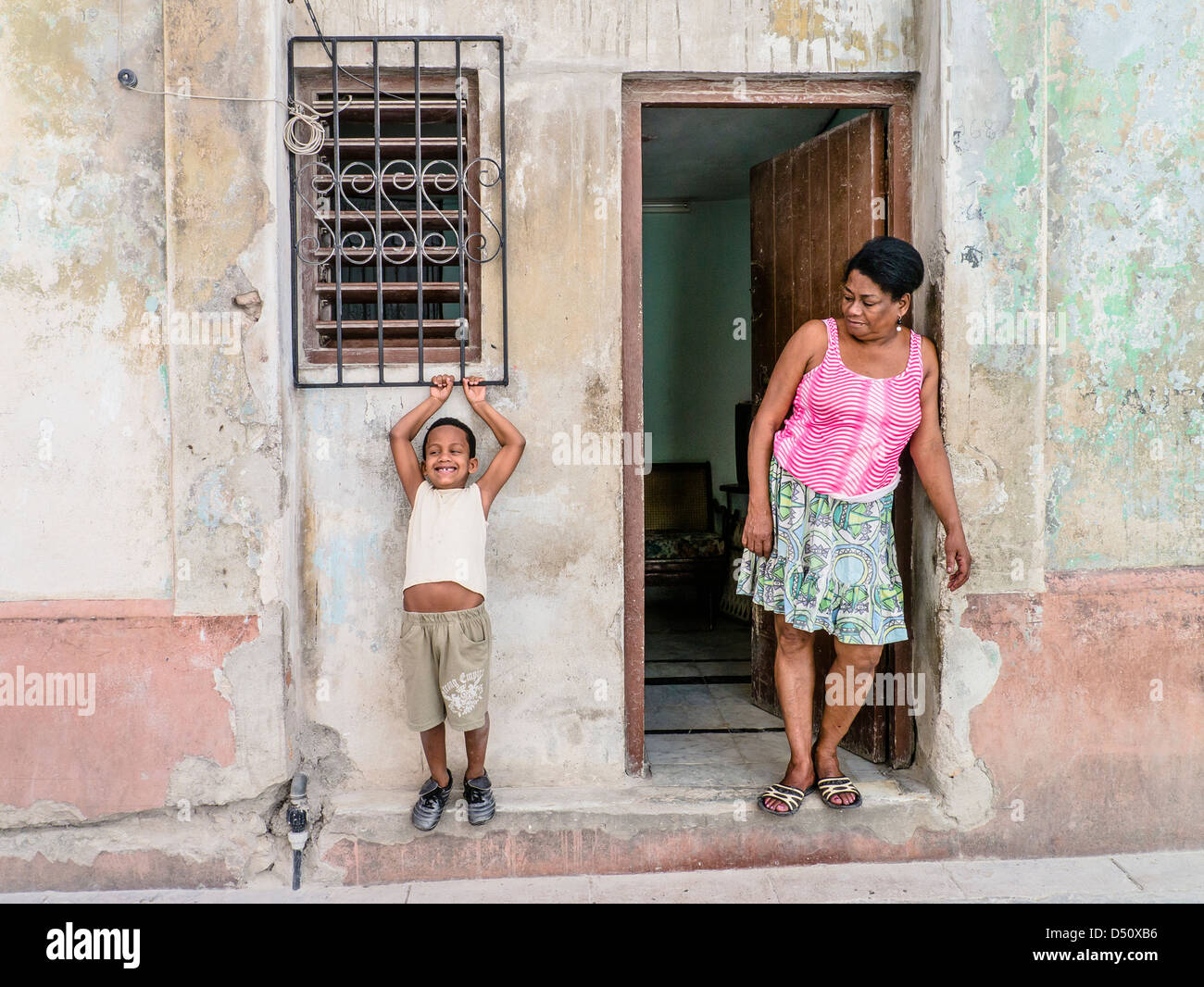 An 8-10 year old Hispanic Cuban boy holds on to an iron window grate over a window of his home with his mother looking - Stock Image