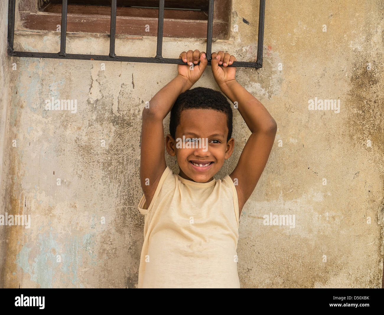 An 8-10 year old Hispanic Cuban boy holds on to an iron window grate over a window of his home with his arms above - Stock Image