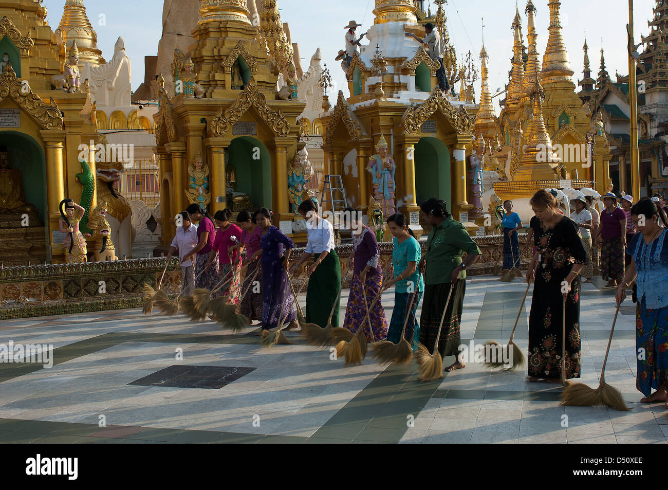 Every evening armies of volunteers sweep the dust from the platform which surrounds the big stupa in Yangon's Shwedagon Stock Photo