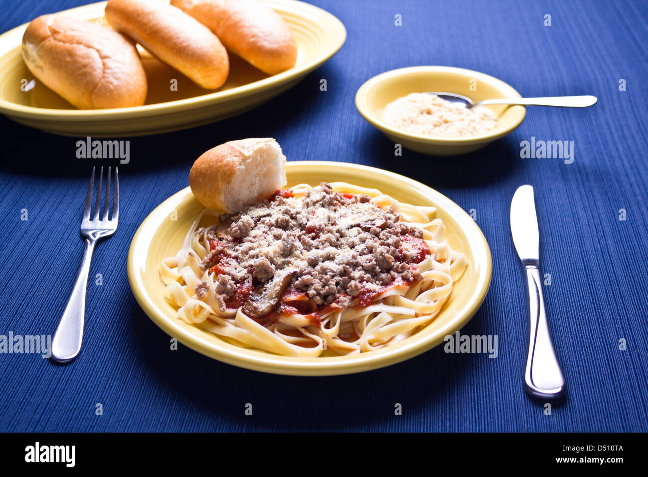Plate of pasta and gravy with parmesan cheese and serving plate with baguettes on it. & Plate of pasta and gravy with parmesan cheese and serving plate with ...