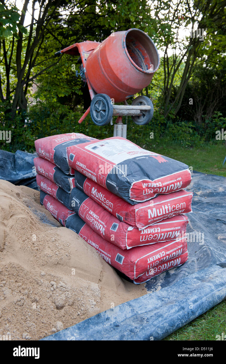 Close-up of building tools & garden landscaping equipment (cement mixer, bags of cement & pile of sand laid on tarpaulin) Stock Photo