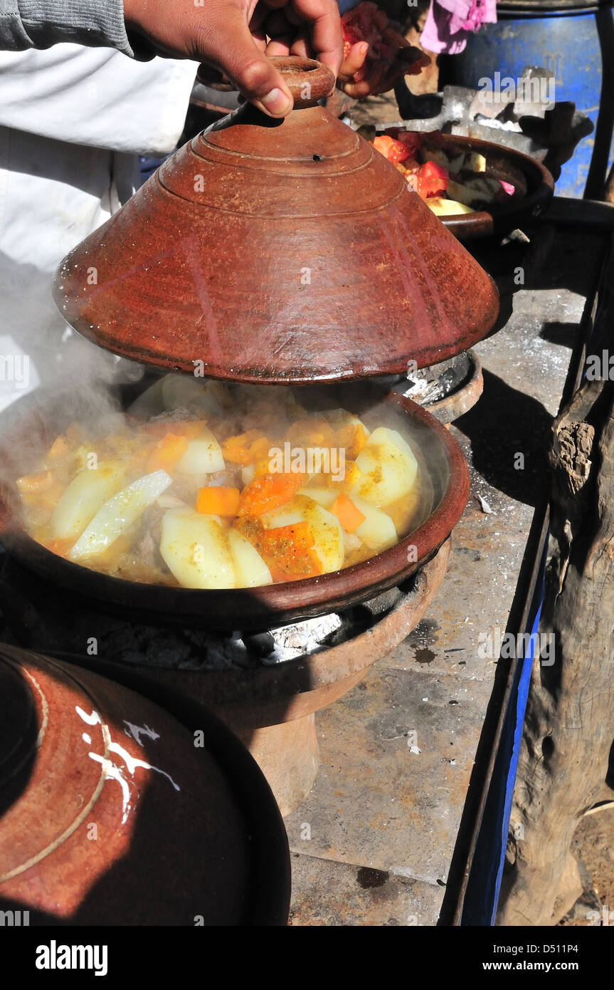 Lid being lifted on tagine being cooked on fire on market day at Jemaa D' Reheat, South of Marrakech, Morocco - Stock Image