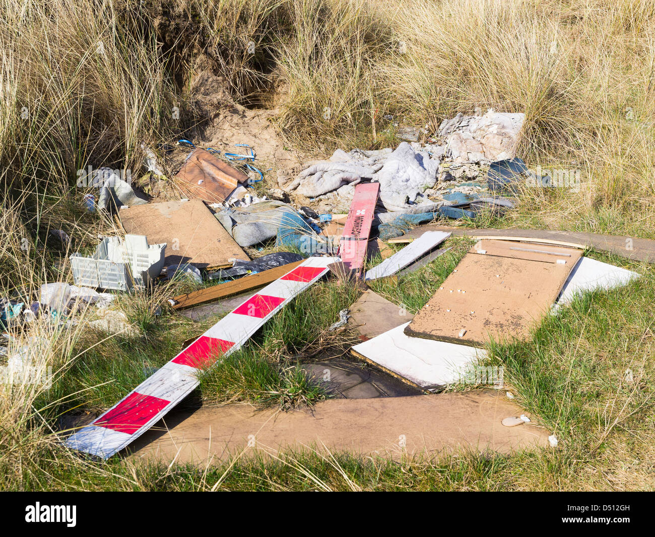 Fly tipping leaves an unsightly mess beside the road - Stock Image