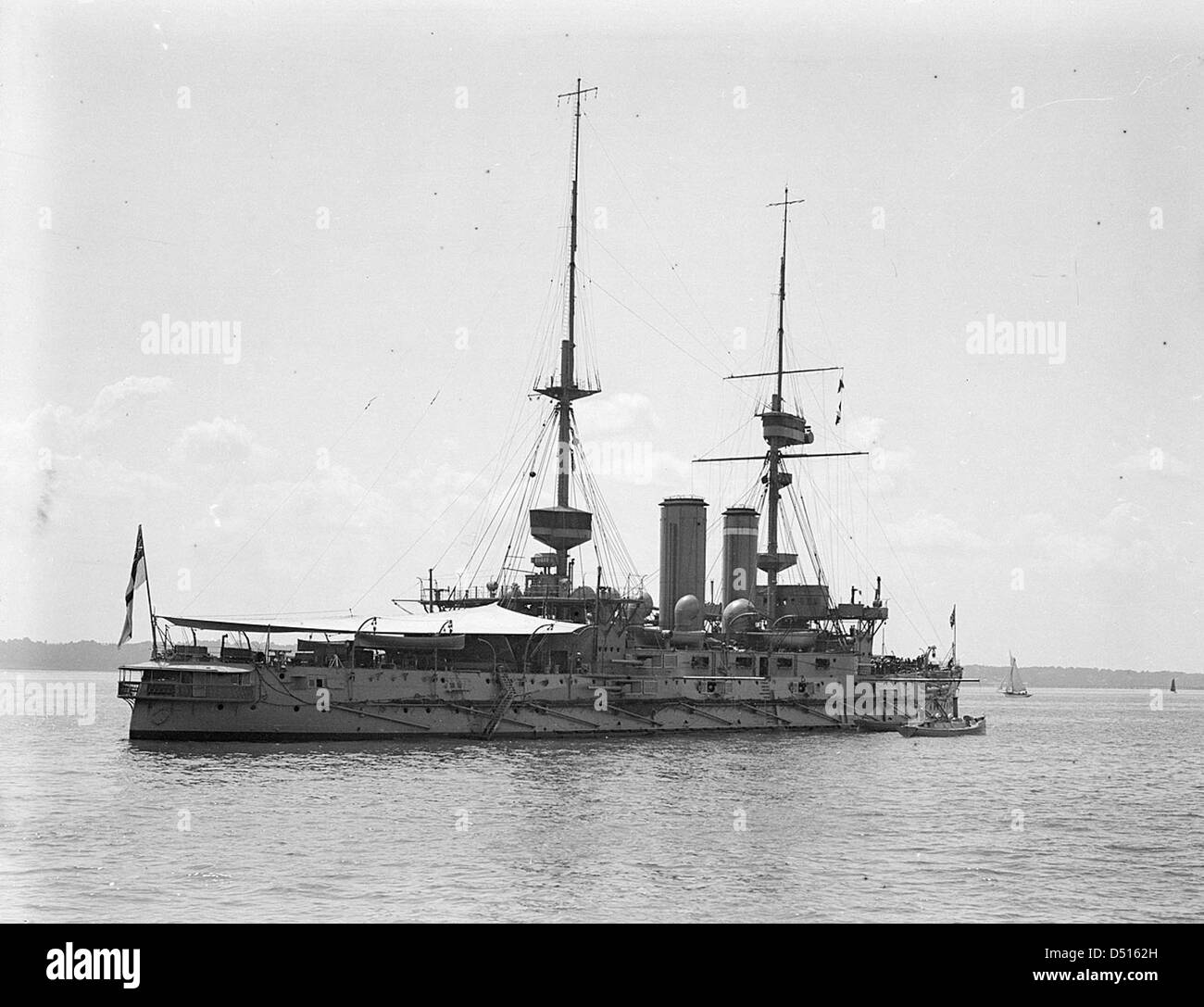 HMS 'Implacable' with awning rigged aft, anchored at Spithead - Stock Image