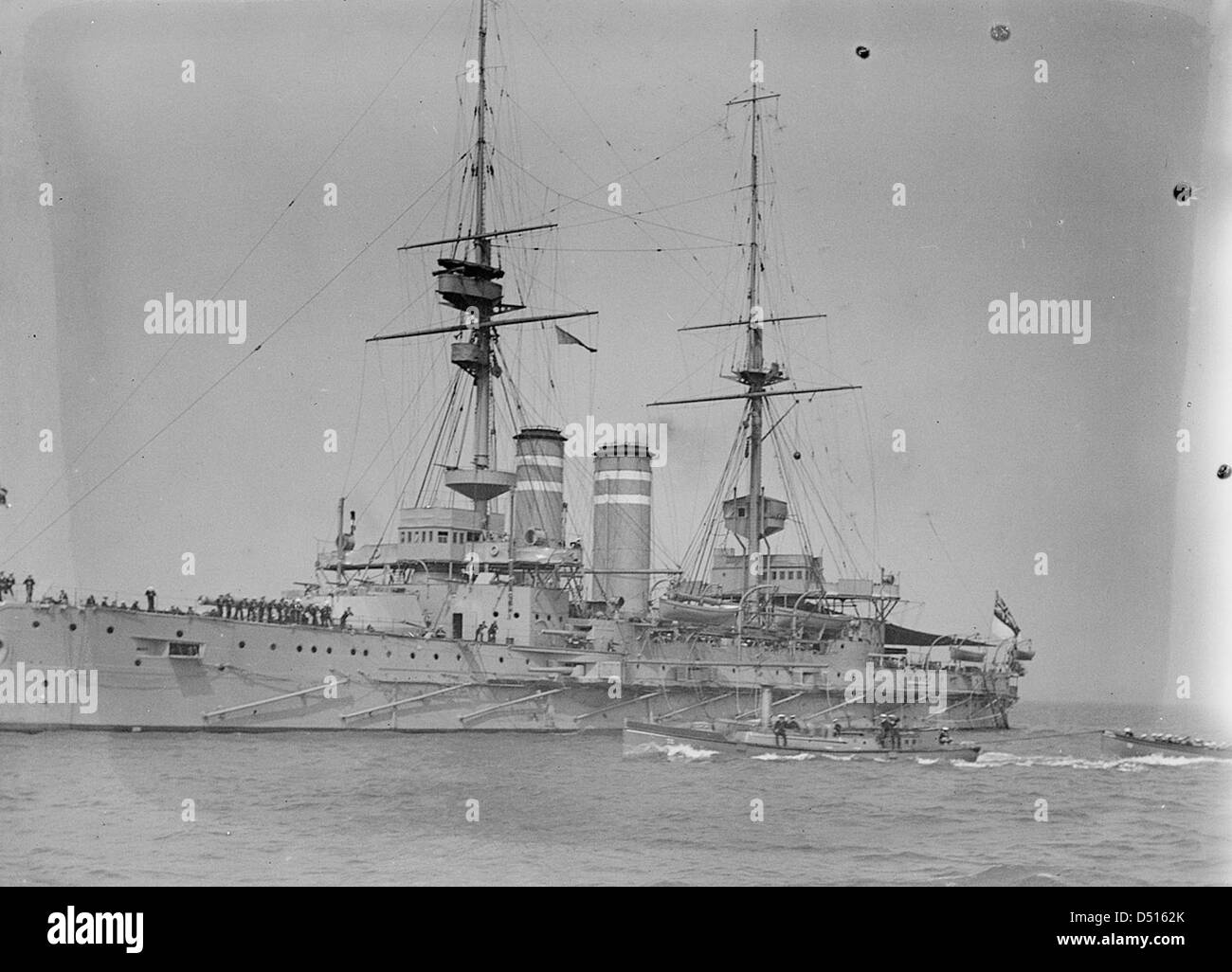 HMS 'Queen' with awning rigged aft, anchored at Spithead - Stock Image