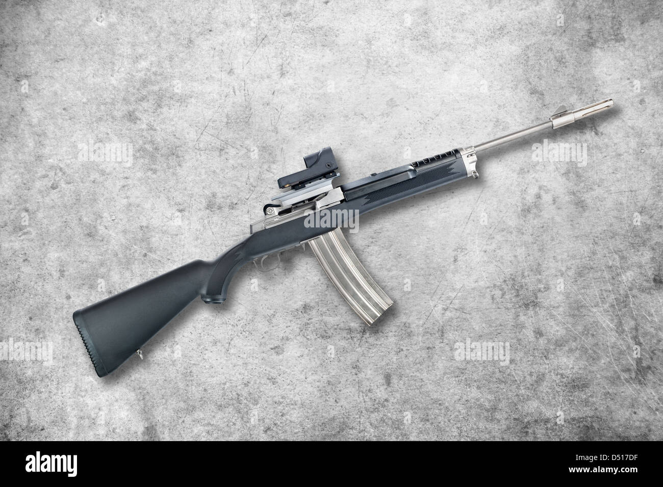 An assault rifle with a 30-round magazine isolated on a black background. - Stock Image