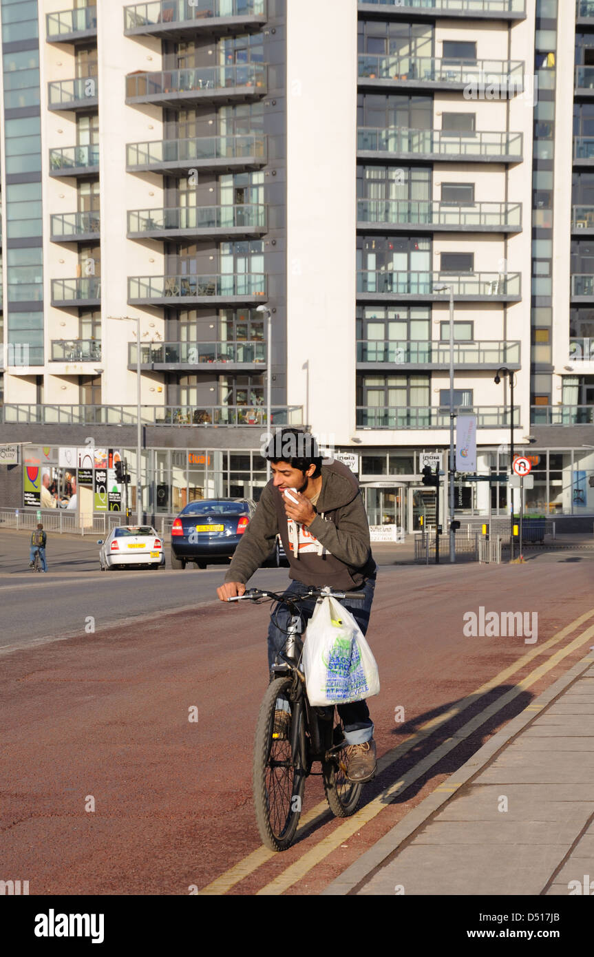 A cyclist breaking the law by using mobile phone whilst steering with one hand and a bag draped over handlebars. - Stock Image