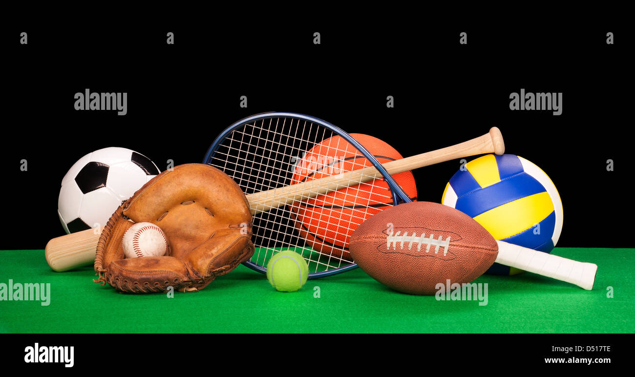 A collection of sports equipment on green felt with clack background. - Stock Image