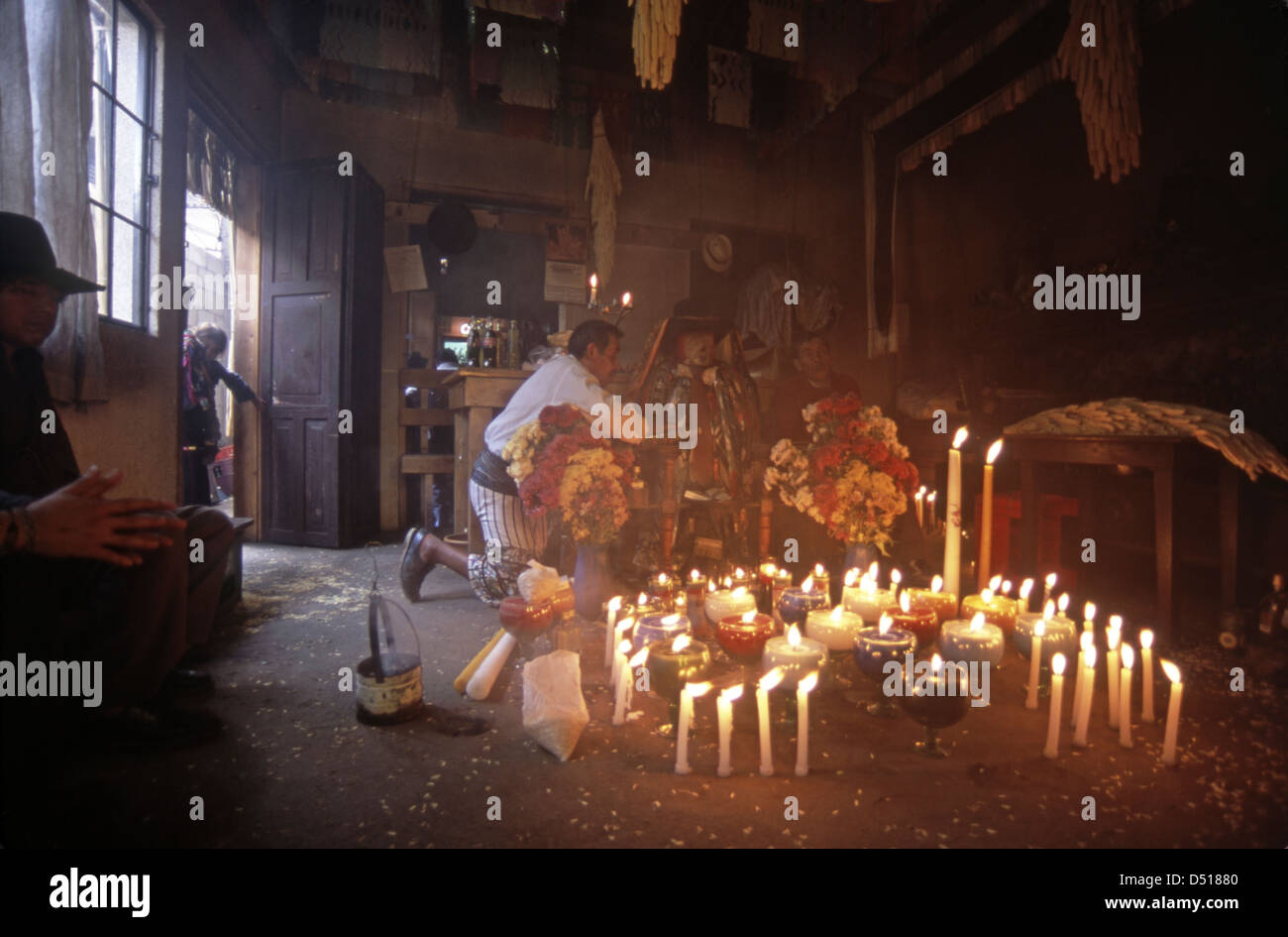 Locals pay respects to maximon at a candlelit shrine in Santiago Atitlan - Stock Image