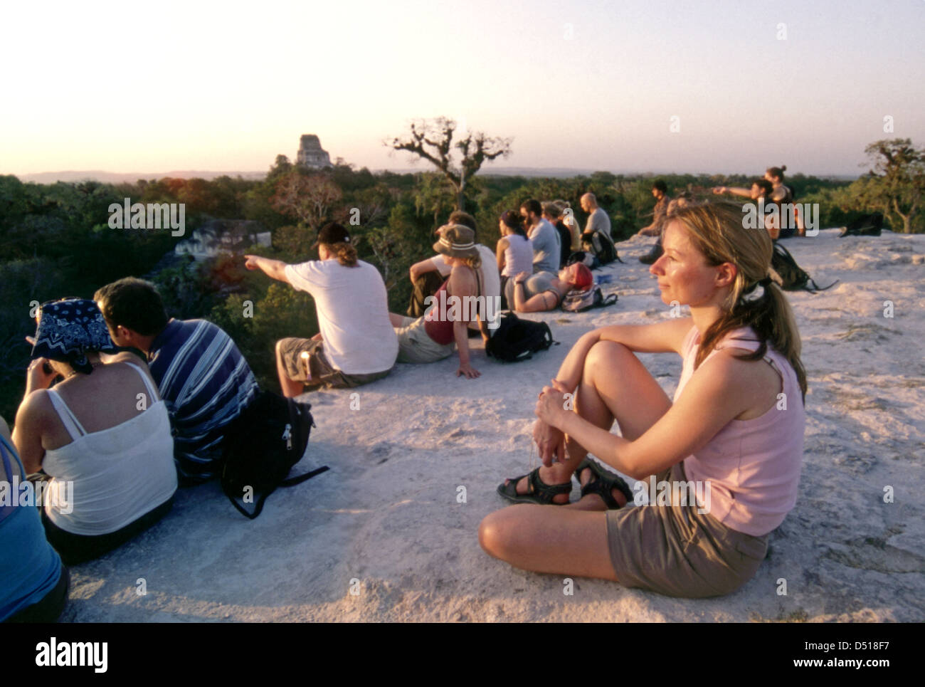 Tourists enjoy the sunset from the top of temple iv 4 at Tikal - Stock Image