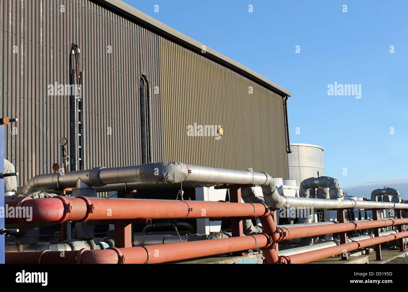 Pipes on exterior of modern factory building. - Stock Image