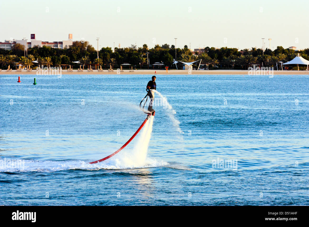 Flyboard Water Jet propulsion demonstration in front of the beach, Abu Dhabi, United Arab Emirates - Stock Image