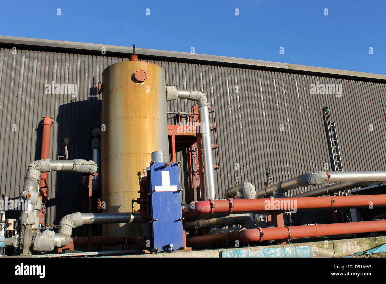 Exterior of modern industrial building with pipes and tank. - Stock Image