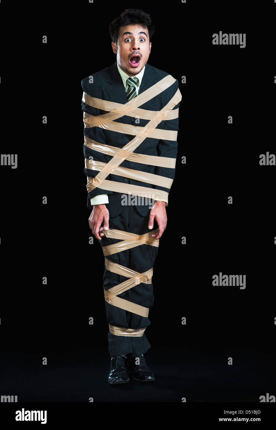 Businessman tied up with adhesive tape looking shocked Stock Photo
