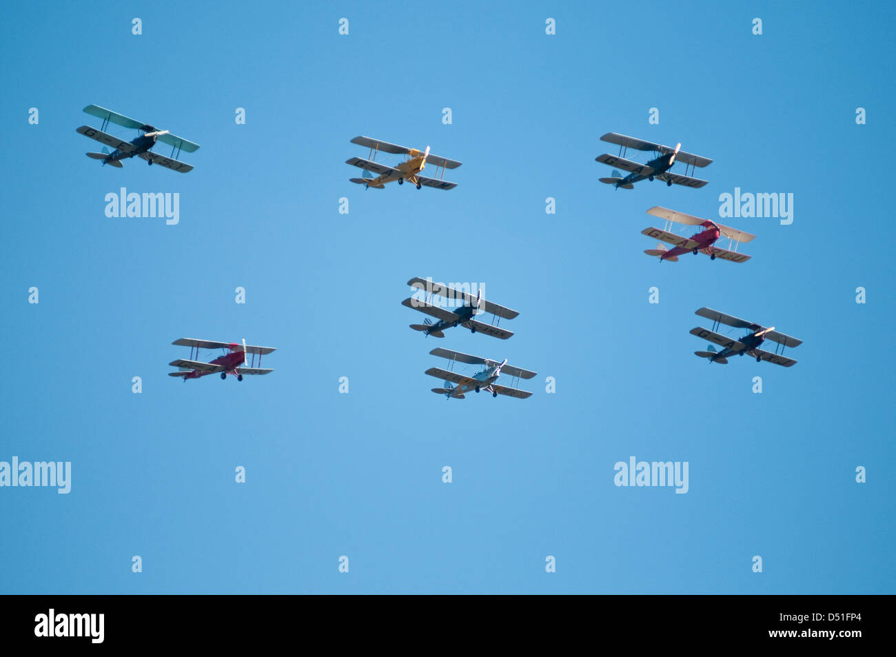 A group of eight vintage bi-planes flying in formation, seen from below against a clear blue sky. - Stock Image