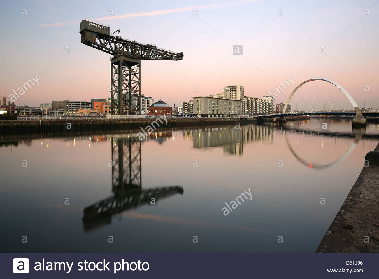 Glasgow Finnieston crane and Clyde arc bridge reflecting on the River Clyde at sunset - Stock Image