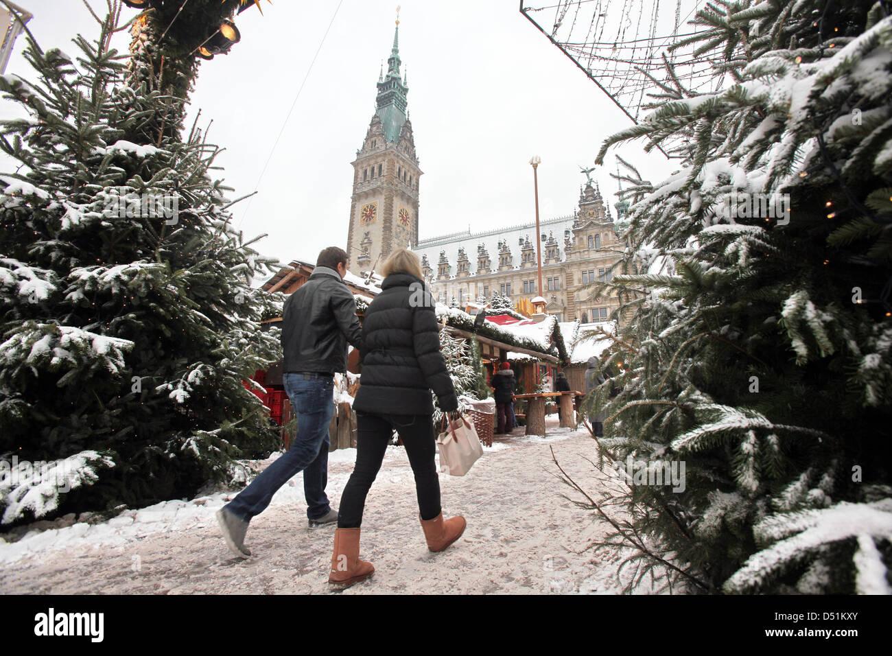 Passanten gehen am Donnerstag (23.12.2010) über den verschneiten Weihnachtsmarkt vor dem Rathaus in Hamburg. - Stock Image