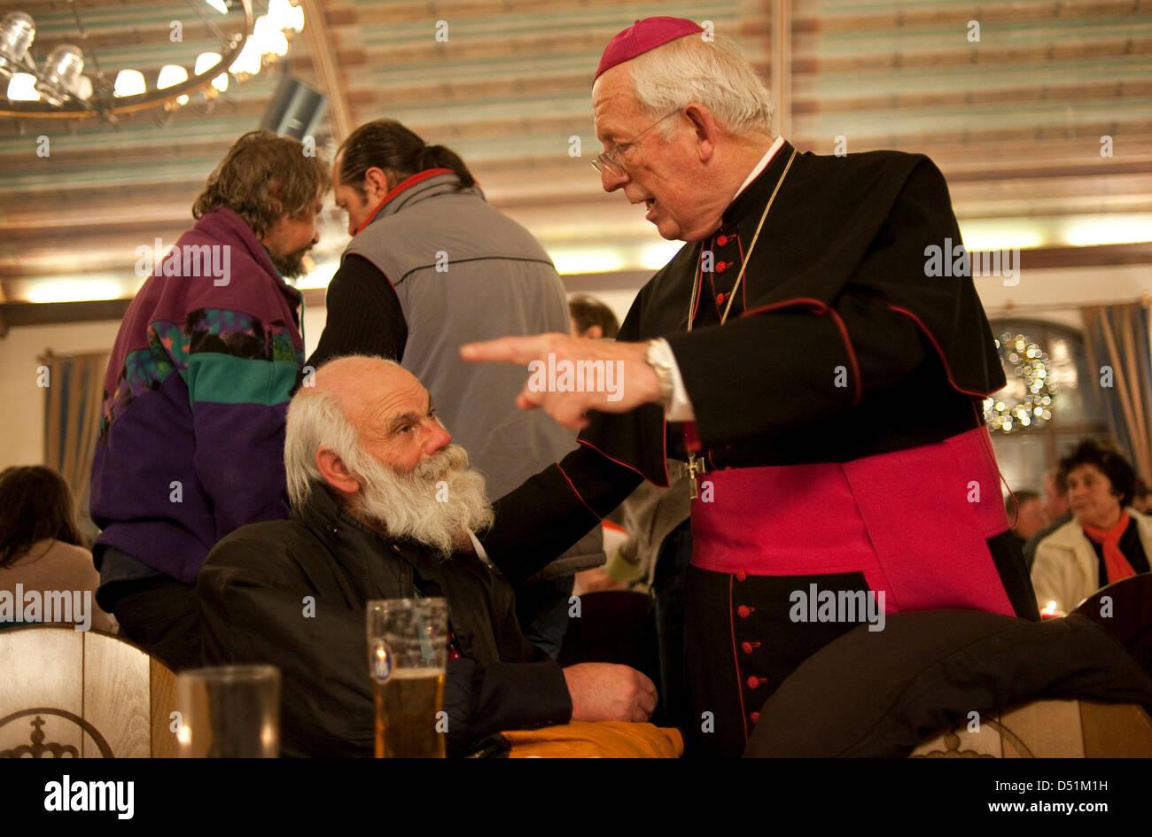 Munich suffragan bishop Engelbert Siebler (R) talks to a homeless man at Hofbraeuhaus inMunich, Germany, 24December - Stock Image