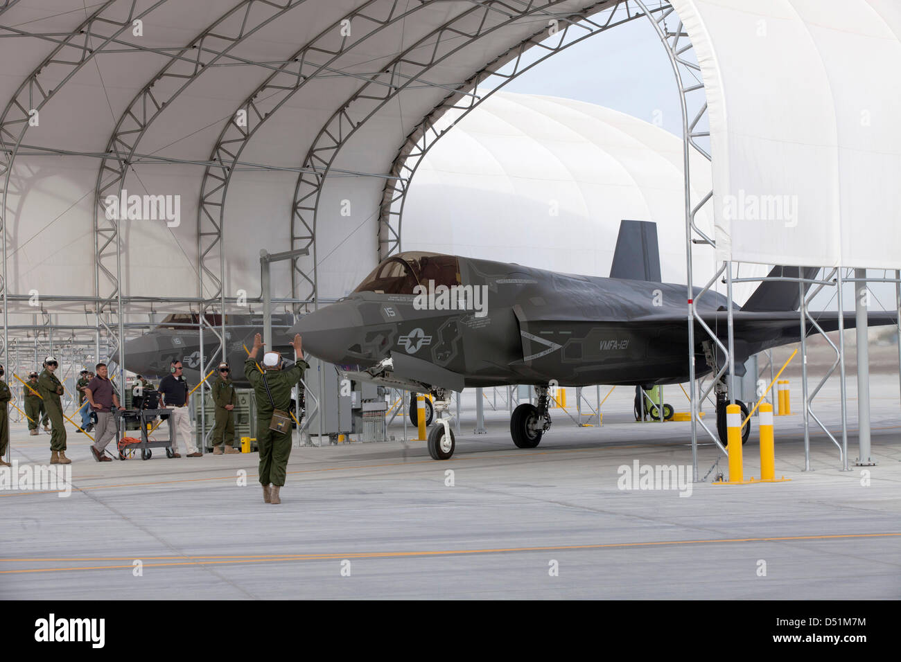 A US Marine Corps F-35B Lightning II stealth fighter aircraft is directed out from a hanger as it makes the first - Stock Image