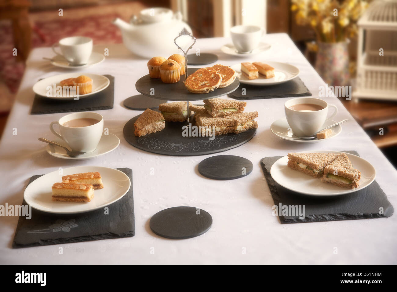Afternoon tea table setting using welsh slate placemats and coasters in a home in south Wales UK & Afternoon tea table setting using welsh slate placemats and coasters ...