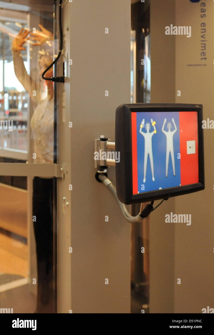 A woman stands inside a body scanner at the airport in Hamburg, Germany, 27 September 2010. Two such devices will - Stock Image