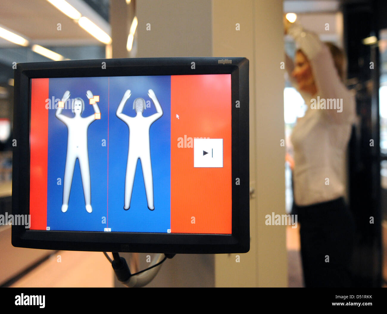 A woman stands inside a body scanner at the airport in Hamburg, Germany, 27 September 2010. Two of such devices - Stock Image