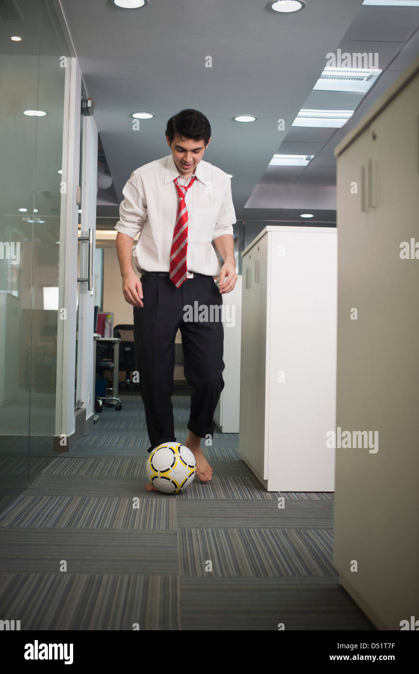 businessman playing with a soccer ball in office