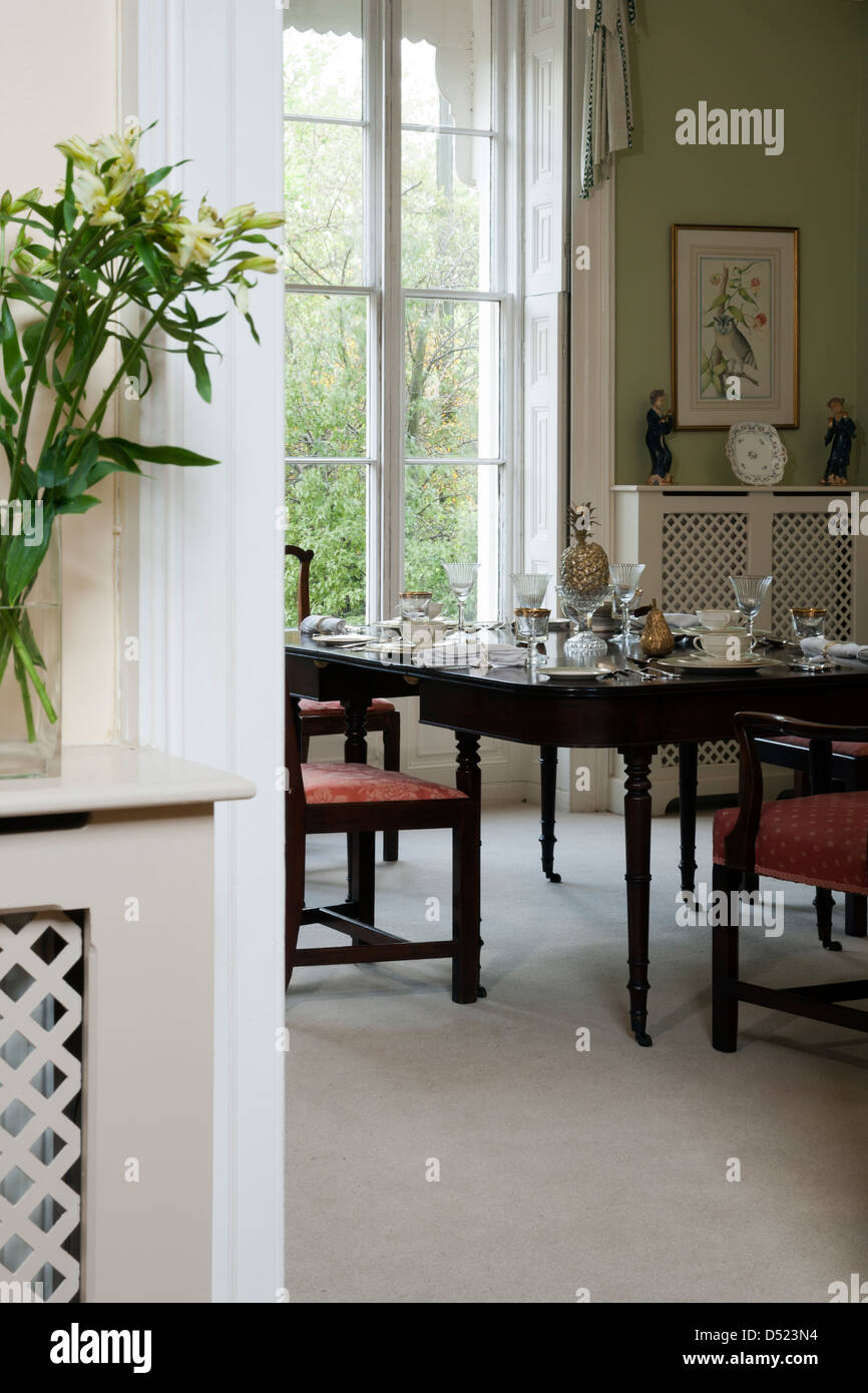 A view through a doorway to a traditional dining room with a laid table. - Stock Image