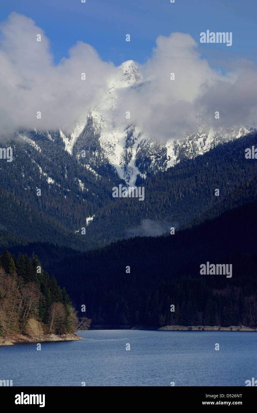 Capilano Lake watershed reservoir with the Lions Mountains under clouds in the background, Vancouver British Columbia - Stock Image