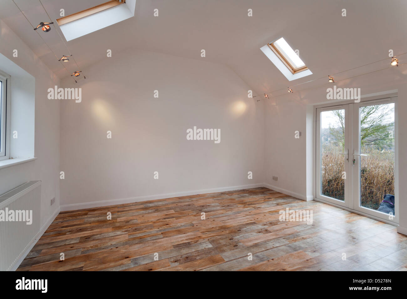 A large new unoccupied white painted high ceilinged empty room with Velux skylights. - Stock Image