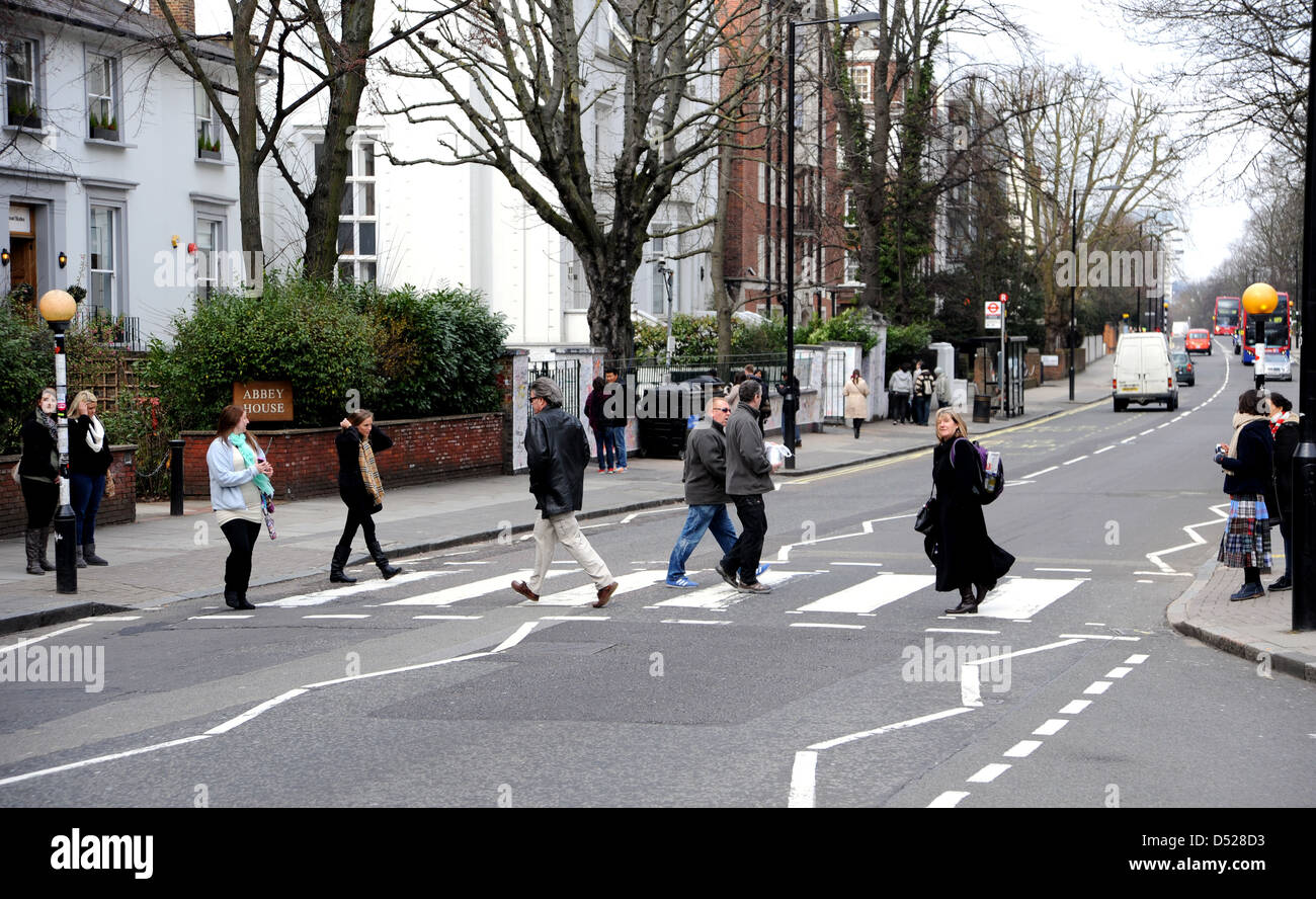 Tourists Walk Across The Famous Pedestrian Zebra Crossing In Abbey Road St Johns Wood London Made By Beatles