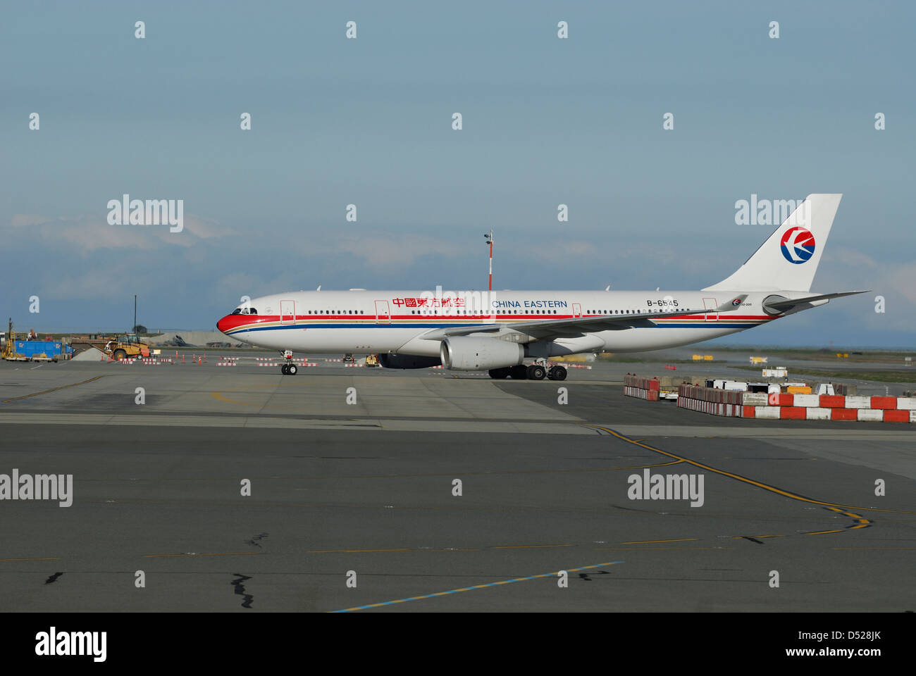 China Eastern Airbus taxiing into Vancouver International airport terminal. - Stock Image