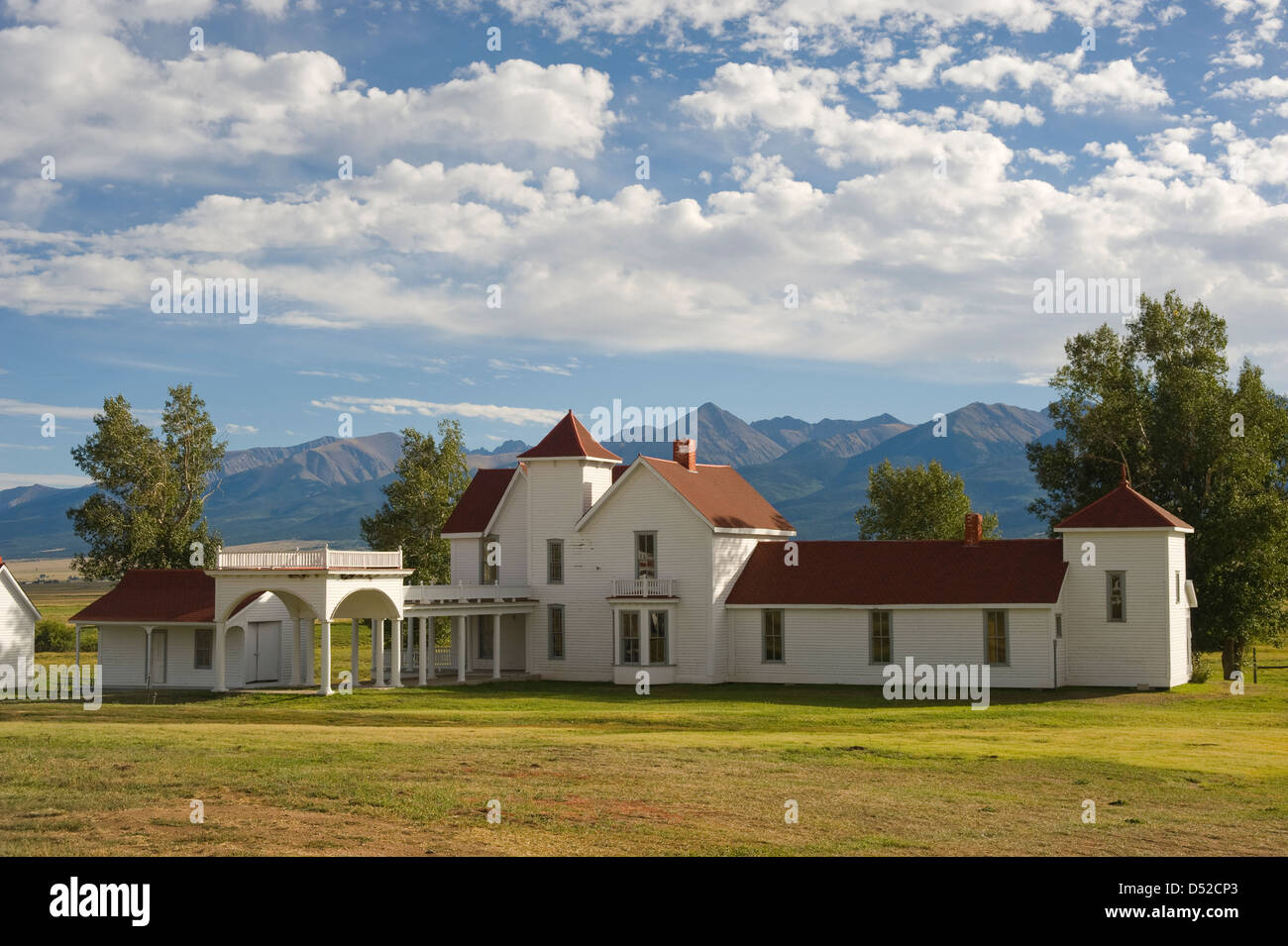 An old mountain ranch sits in the middle of hay meadows and fields, with the Sangre de Cristo Mountain Range in - Stock Image