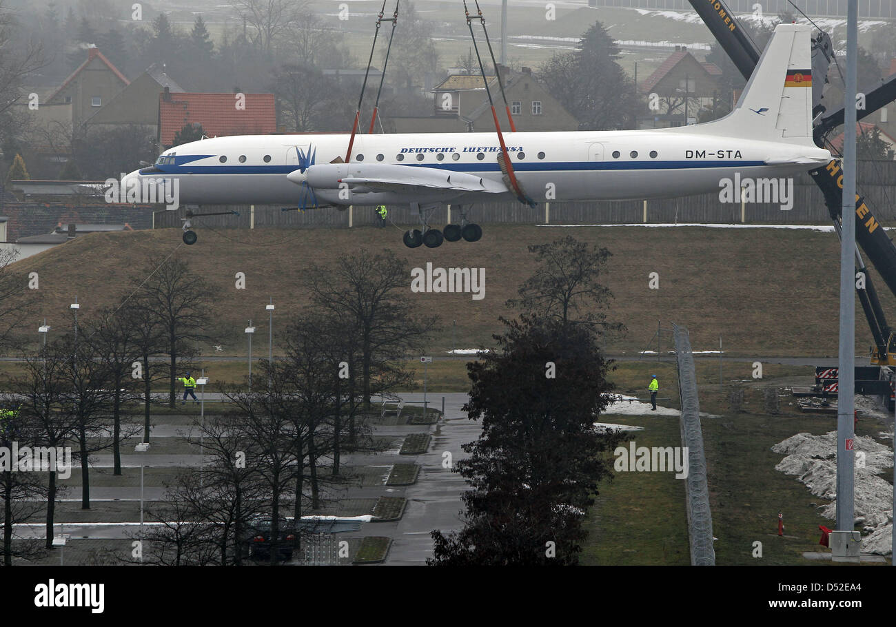 A crane carries an Ilyushin IL 18 airplane over the parking space of the airport Leipzig/Halle in Schkeuditz, Germany, Stock Photo