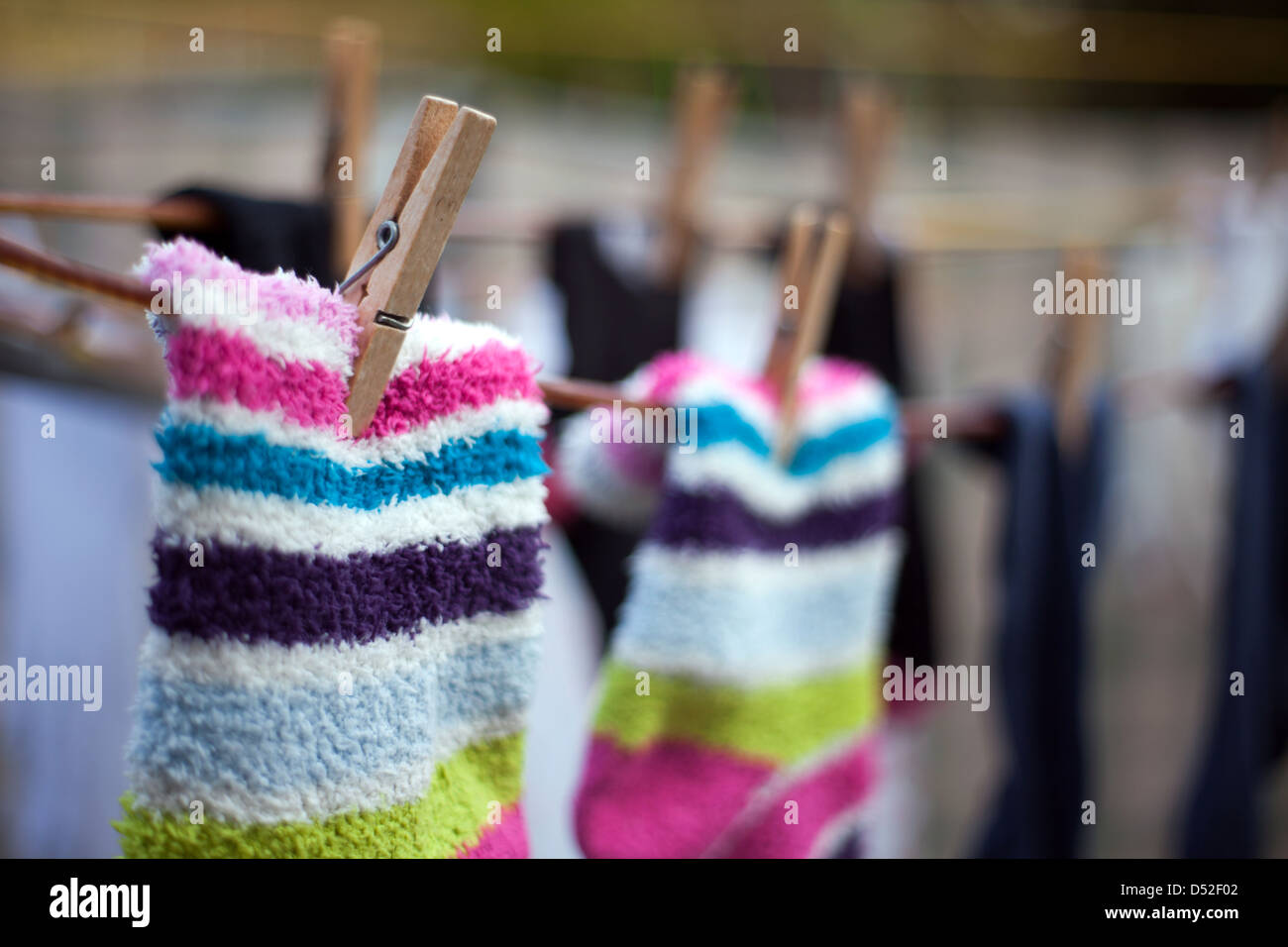 Colourful woolly socks pegged on to washing line - Stock Image