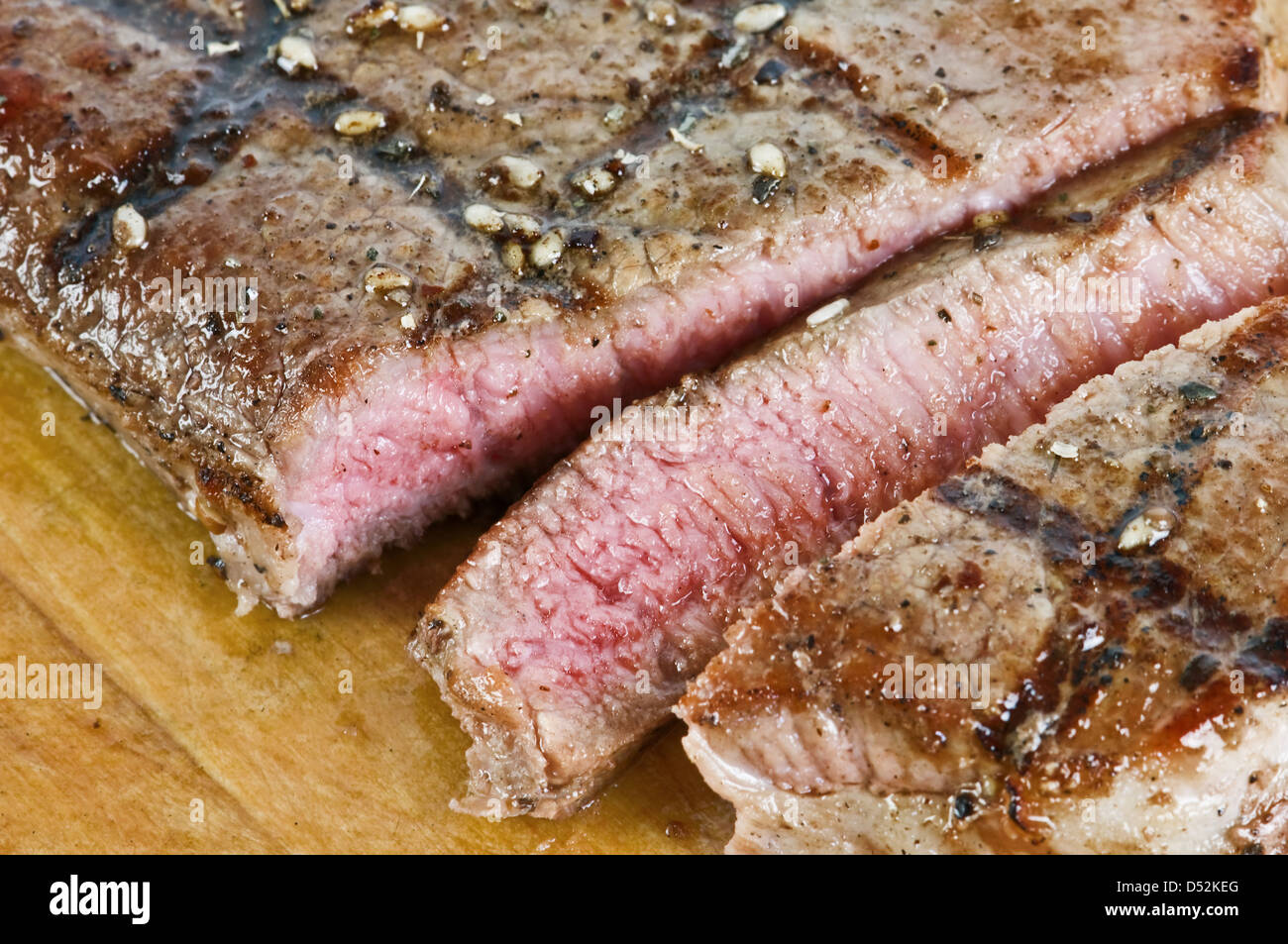 juicy striped steak on wood table - Stock Image