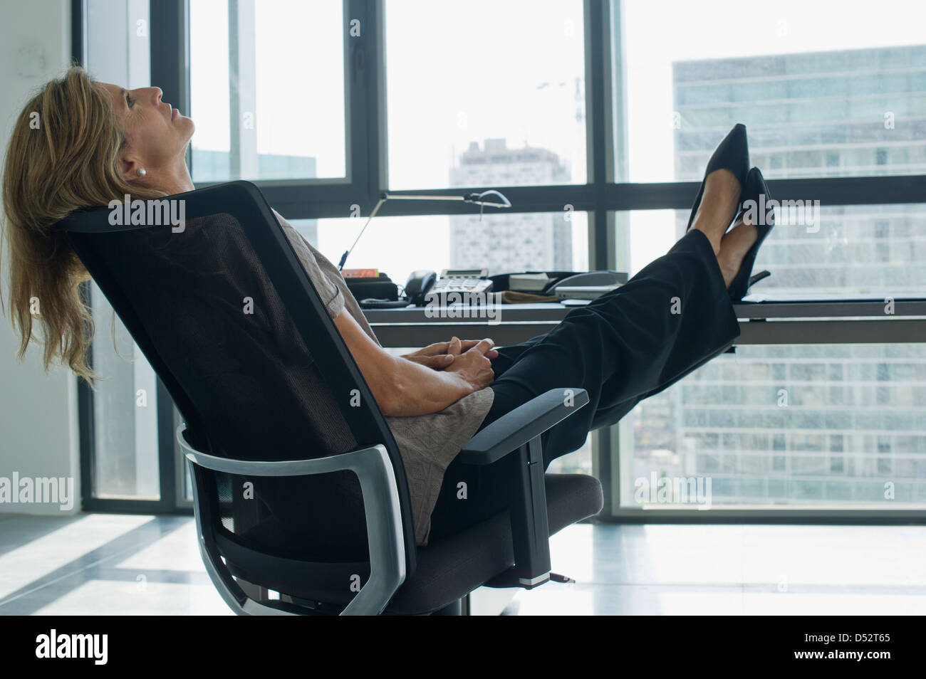 Businesswoman leaning back in chair with feet up on desk - Stock Image