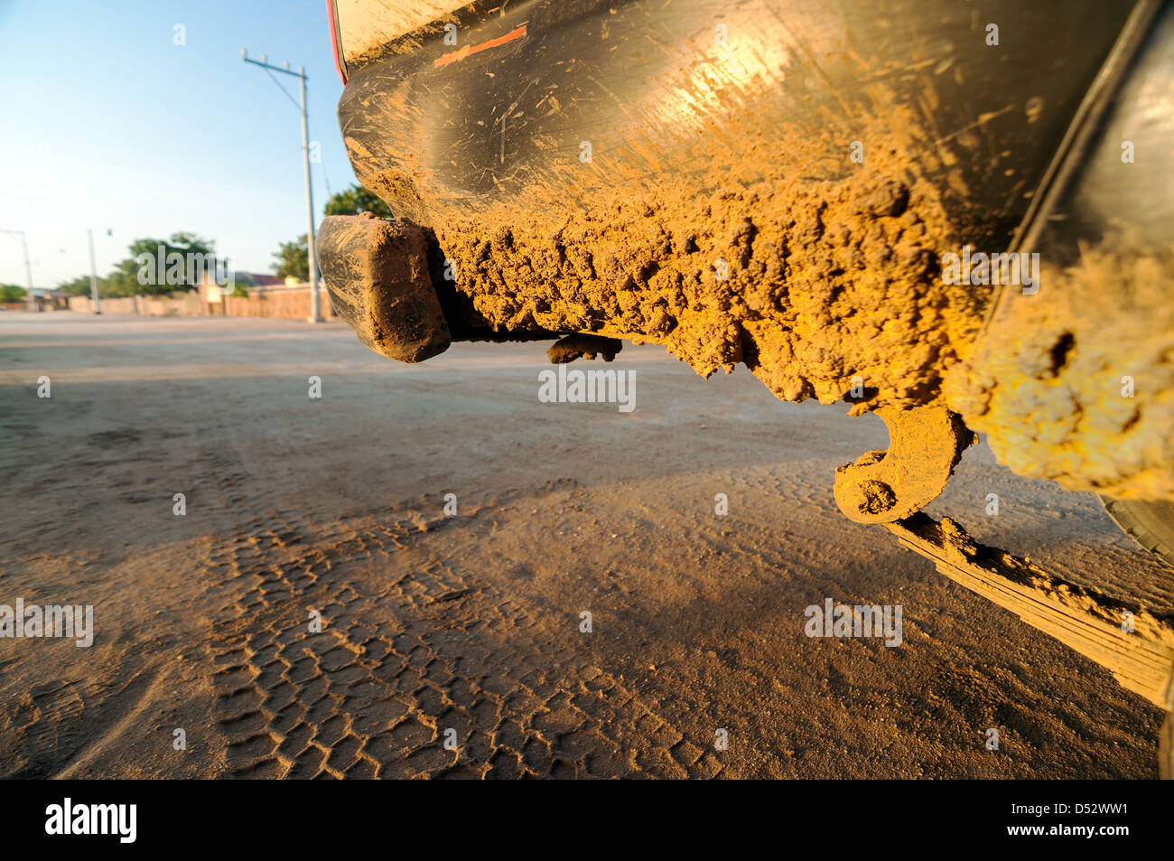 A muddy dirty SUV with a beach town in the background - Stock Image