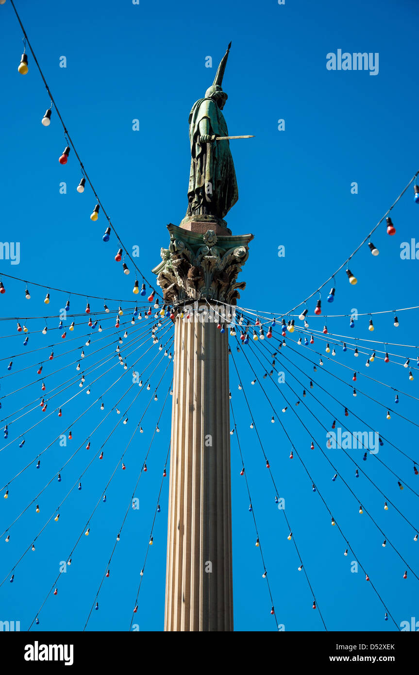 Public statue in Montevideo with blue sky and Christmas lights - Stock Image