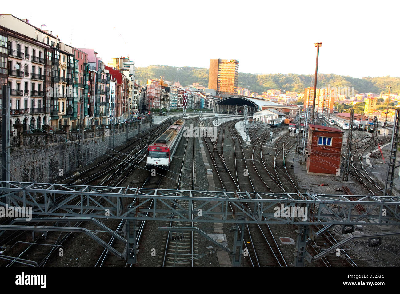 Railroad tracks and catenary, with crossings of roads and sidewalks. Bilbao, Spain. Stock Photo