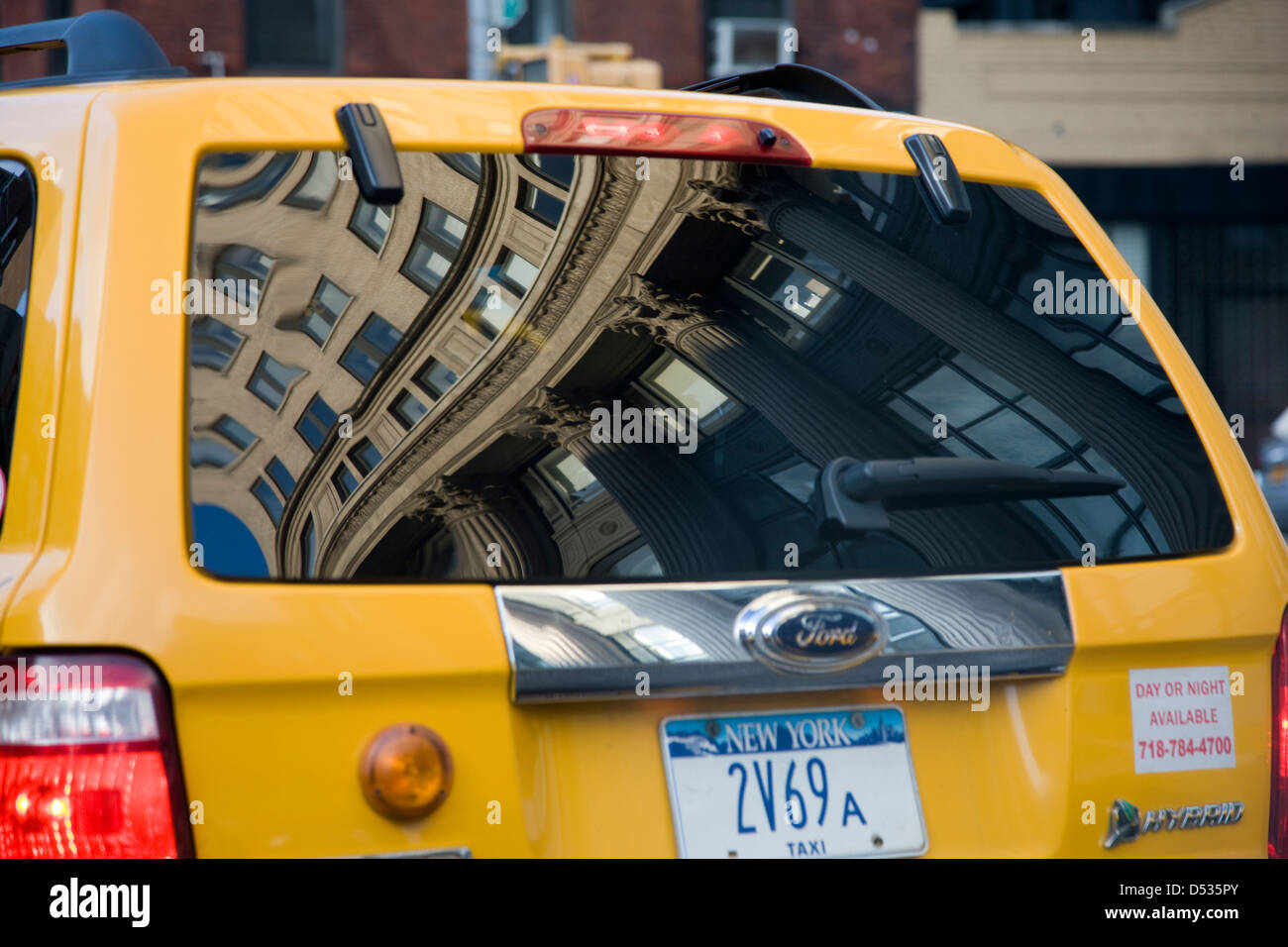 Building facade with Corinthian columns reflected in the back windscreen of a yellow cab, New York - Stock Image