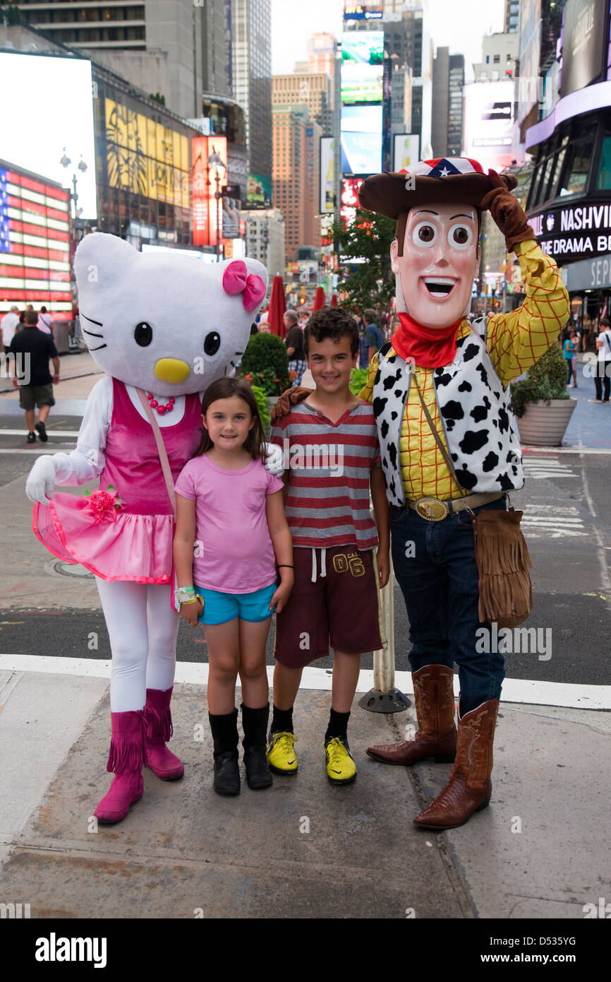 Hello Kitty and Toy Story Woody cartoon character costumes posing with children in Times Square, New York - Stock Image
