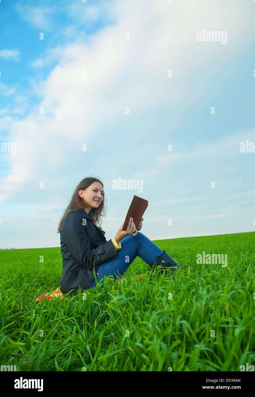 Teen girl reading the Bible sitting outdoors at sunset time - Stock Image