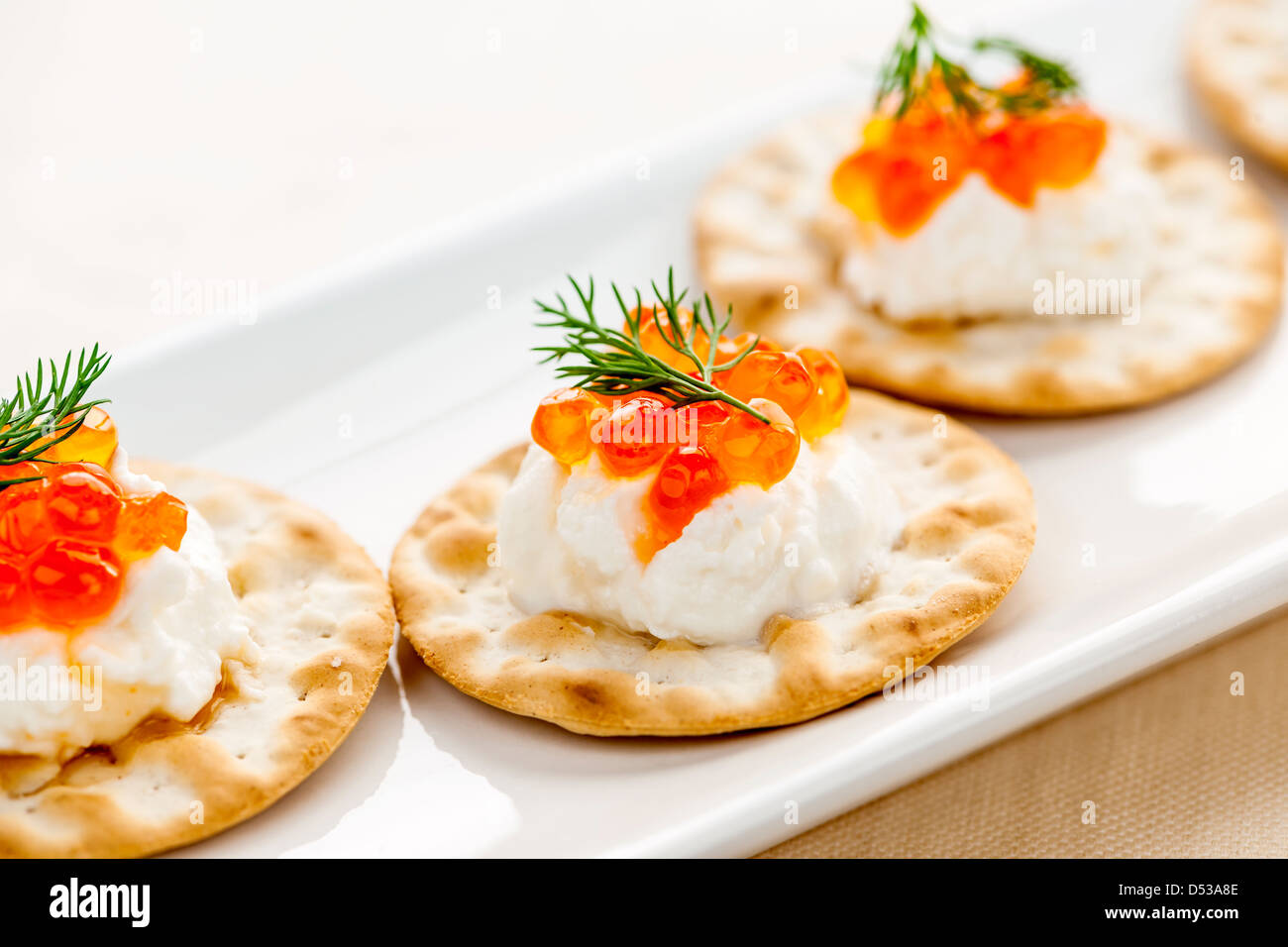 Closeup of caviar and cream cheese appetizer on crackers - Stock Image