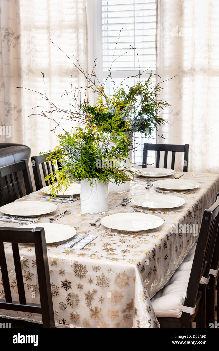 Dining table decorated for Christmas with eight place settings and evergreen centerpiece Stock Photo